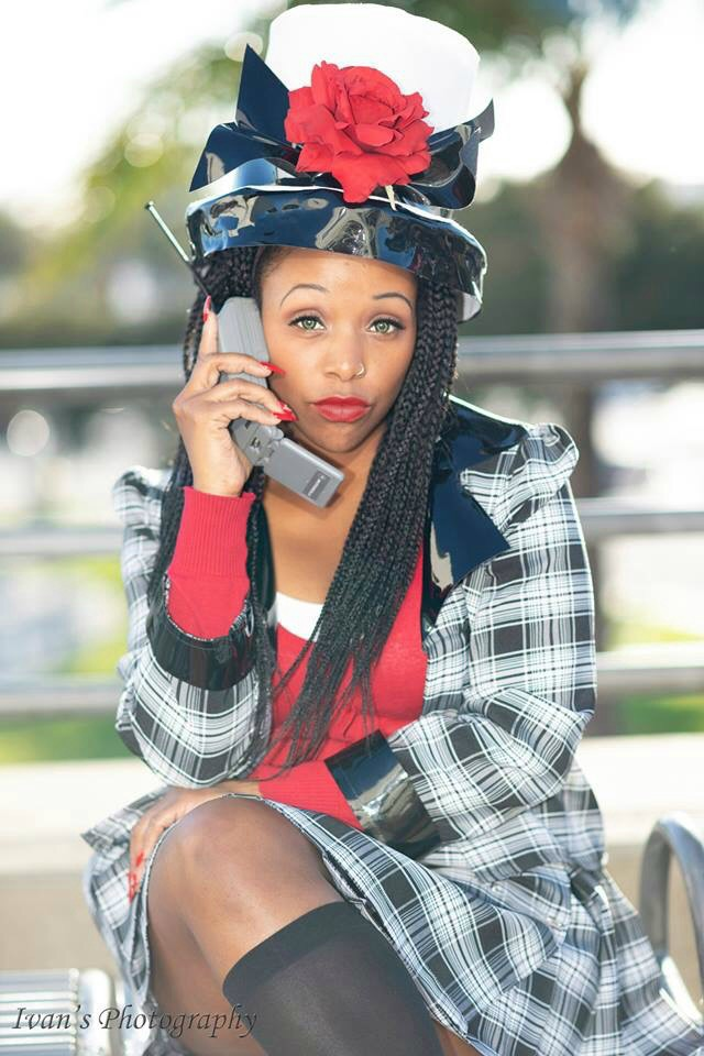 Francheezy dressed as Dionne Davenport from Clueless. Red long sleeve deep cut top with a white undershirt, black and white plaid pattern skirt, jacket, and matching hat with knee high black stockings. She is sitting cross legged holding an old mobile from the 90s.