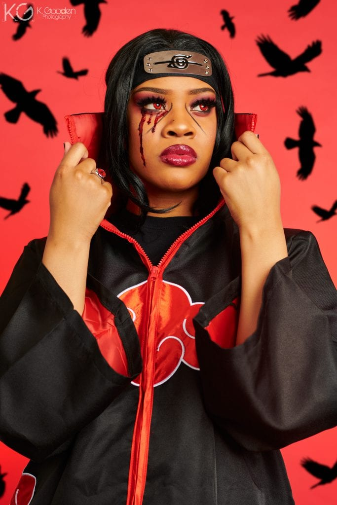 Itachi Uchiha from Naruto. long black satin trench coat zip up with red clouds lined with white embroidery and red lining in jacket. red ring on right hand ring finger, black hair, red contacts, smoky red/black eye shadow, black lines under the eyes out to mid cheeks, fake blood coming from the right eye.