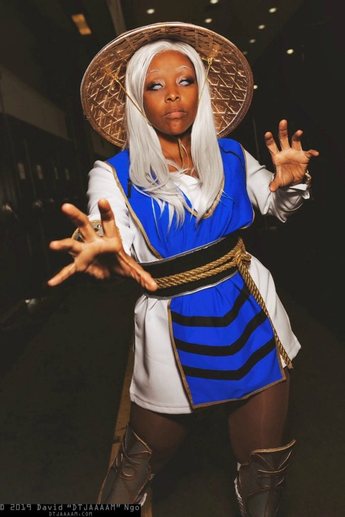 Francheezy cosplaying as Raiden from Mortal Kombat with a white wig, white contacts, and the blue and white uniform.